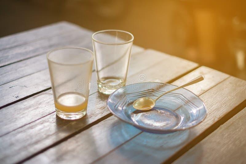 Verre vide de thé chaud dedans avec la soucoupe et la cuillère sur la table en bois photo libre de droits