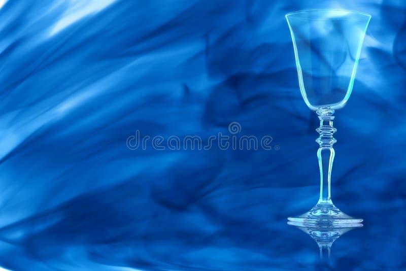 Verre vide de vin rouge sur la tige avec le fil enveloppé dans la fumée bleue image libre de droits