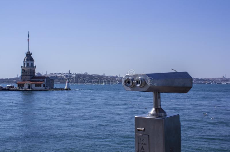 Verrekijkers door het overzees die Bosphorus en het Aziatische deel van Istanboel overzien De Toren van het meisje op de linkerka stock fotografie