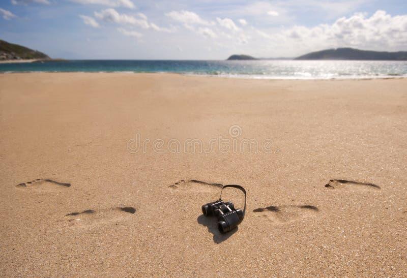 Verrekijkers en voetafdrukken op een strand. stock foto