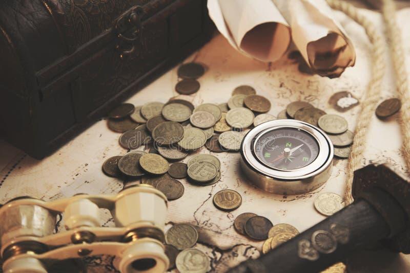 Verrekijkers, kompas, mes en muntstukken op kaart royalty-vrije stock fotografie