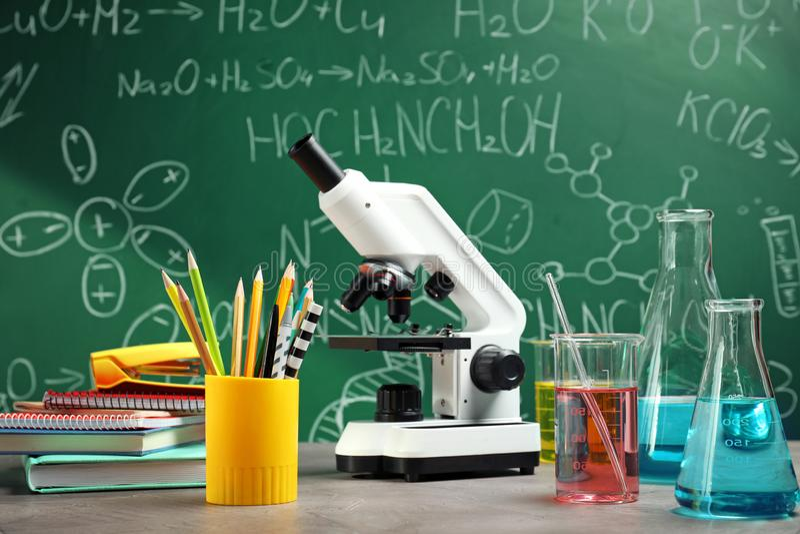 Verrerie, microscope et papeterie de laboratoire sur la table photographie stock libre de droits