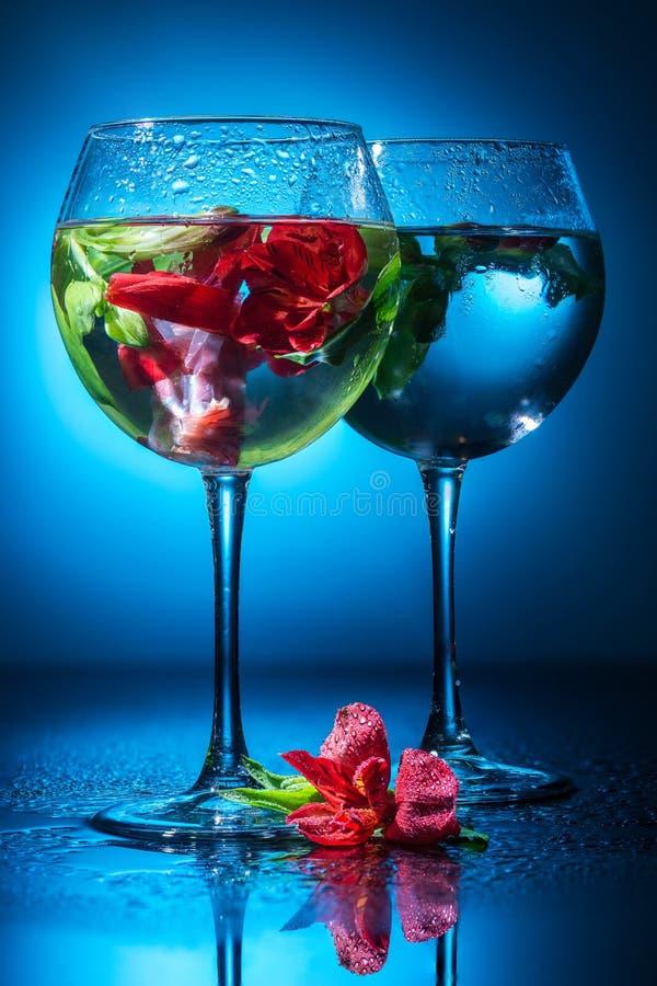 Verres à vin avec l'eau et des fleurs image stock