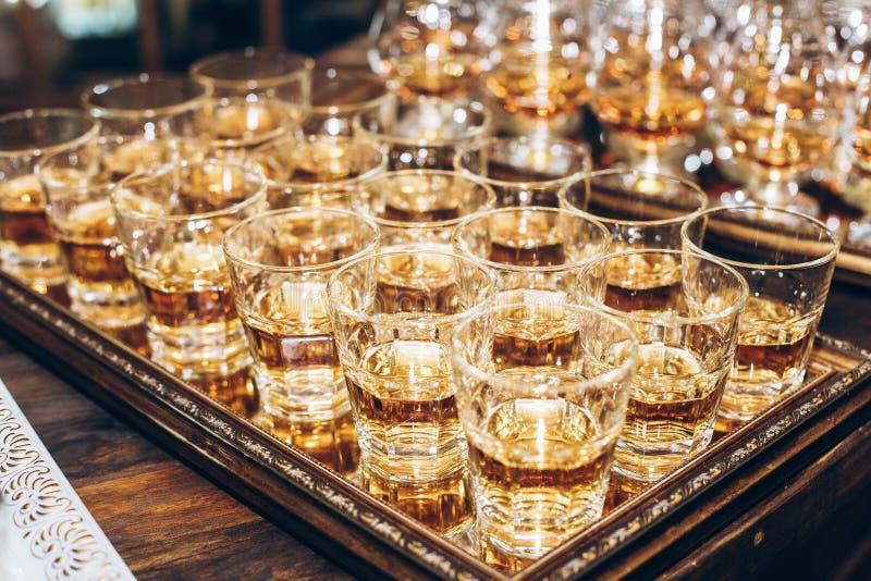 Verres élégants avec le cognac ou le whiskey sur la table au recep de mariage image stock