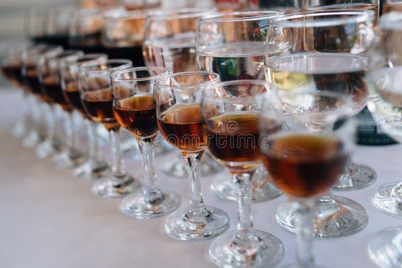 Verres avec de l'alcool sur une table dans un restaurant sur une nappe blanche image libre de droits