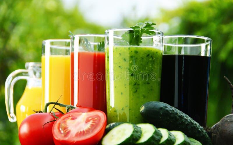 Verres avec des jus de légume frais dans le jardin Régime de Detox photos stock