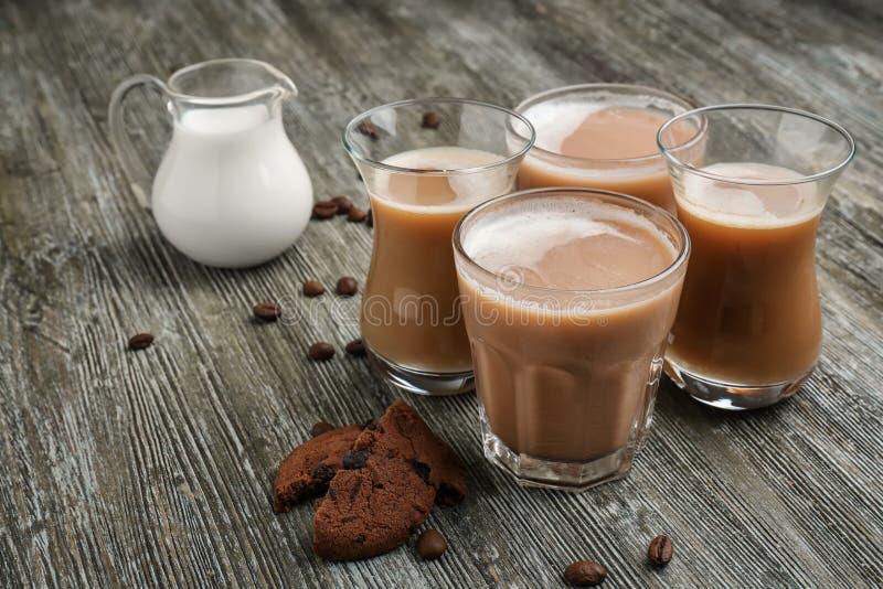 Verres avec du café et la cruche aromatiques savoureux de lait sur la table en bois photos stock