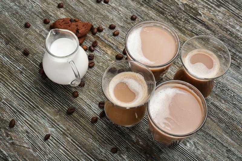 Verres avec du café et la cruche aromatiques savoureux de lait sur la table en bois photo stock