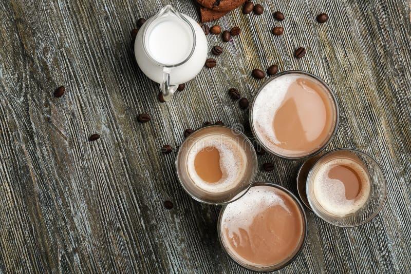 Verres avec du café et la cruche aromatiques savoureux de lait sur la table en bois image libre de droits