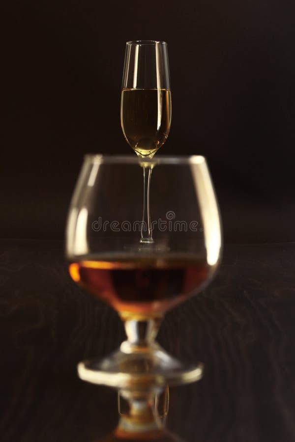 Verres avec du vin blanc et cognac ou whiskey sur la table de miroir Composition en célébrités photographie stock libre de droits