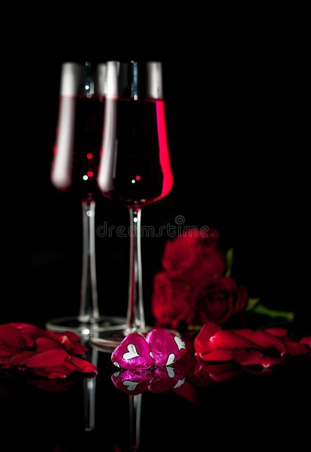 Verres avec le champagne et le chocolat deux roses pour le Saint Valentin photo stock