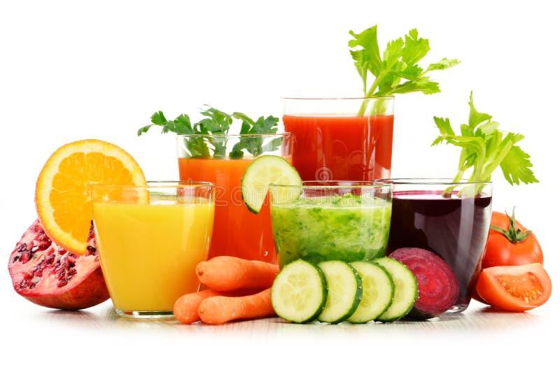 Verres avec les jus organiques frais de légume et de fruit sur le blanc images libres de droits