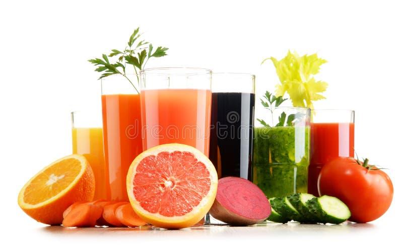 Verres avec les jus organiques frais de légume et de fruit sur le blanc photos stock
