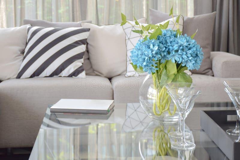 Verres bleu-clair de fleur et de vin sur la table centrale avec l'oreiller noir et blanc rayé et les oreillers gris de ton sur le photo libre de droits