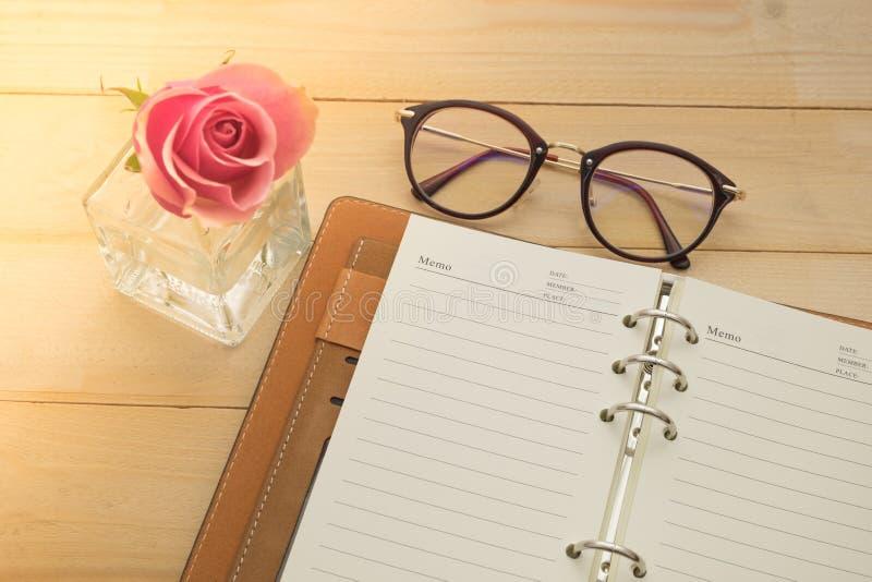 Verres, carnet et rose de rose dans le vase en verre sur le fond en bois photo libre de droits