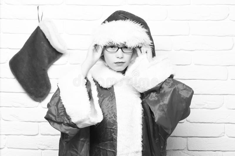 Verres corrects de jeune garçon mignon du père noël dans le chandail rouge et le chapeau de nouvelle année avec Noël ou Noël déco photographie stock