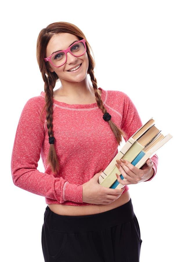 Verres d'écolière et livres de port de se tenir photographie stock