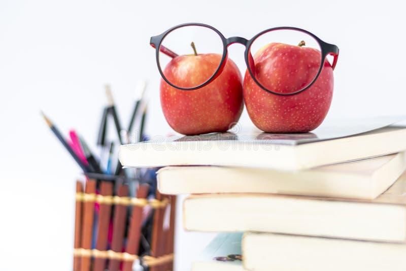 Verres d'oeil et pomme rouge avec des approvisionnements de livre et de papeterie et accessoires sur le fond blanc De nouveau ? l images stock
