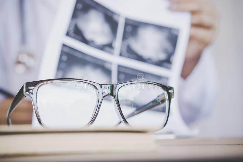 Verres d'oeil sur le bureau avec le fond de tache floue du docteur travaillant dans l'hôpital photo libre de droits