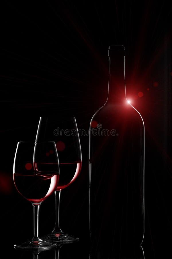 Verres de bouteille et de twowine de vin rouge avec la fusée sur le backgrou noir images libres de droits