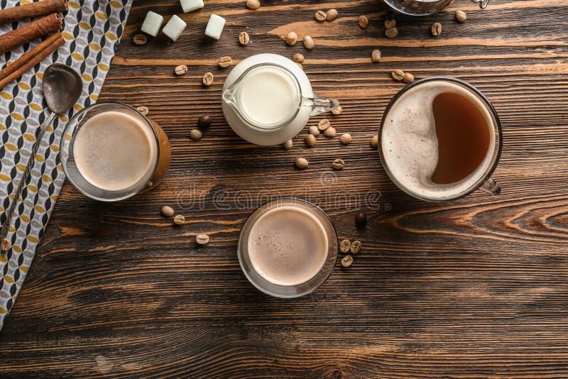 Verres de café aromatique savoureux avec la cruche de lait et de haricots sur la table en bois image libre de droits
