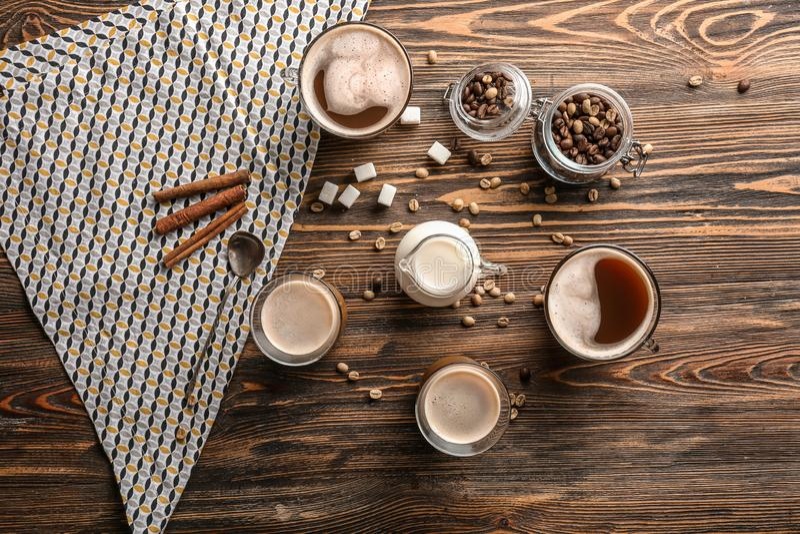 Verres de café aromatique savoureux avec la cruche de lait et de haricots sur la table en bois images stock