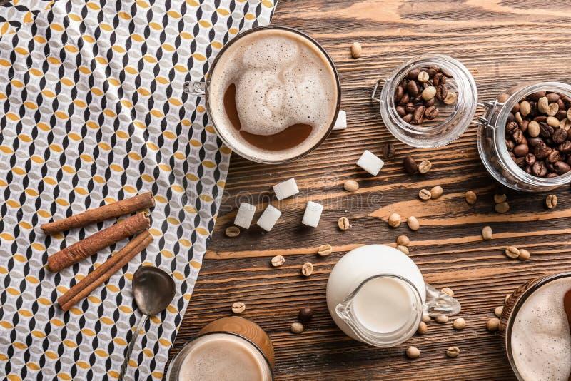 Verres de café aromatique savoureux avec la cruche de lait et de haricots sur la table en bois photo libre de droits