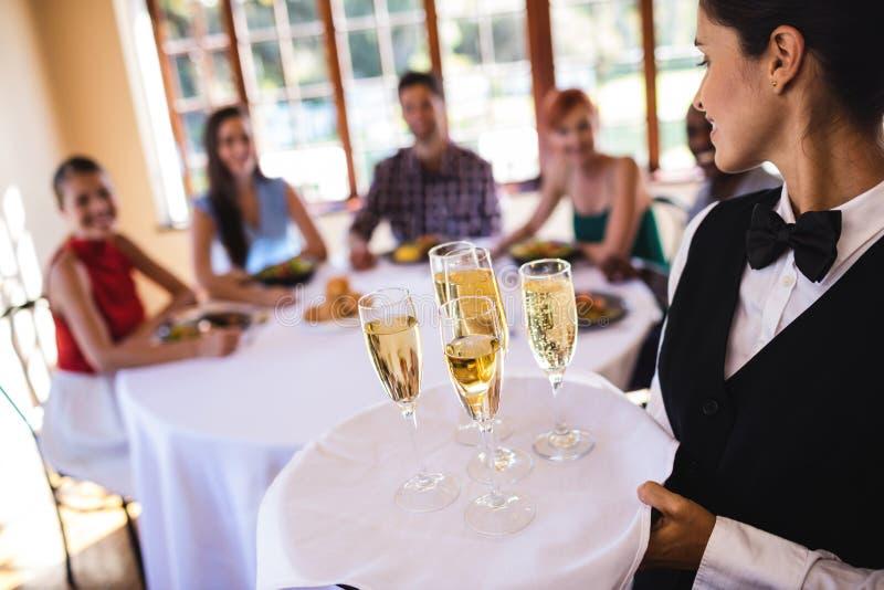 Verres de champagne de serveuse sur le plateau dans le restaurant image stock