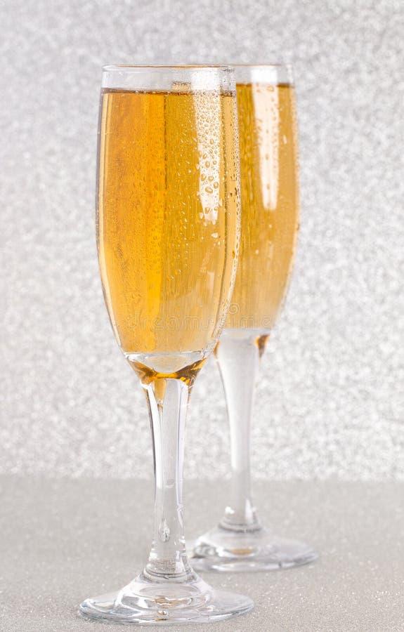 Verres de Champagne sur un contexte argenté de scintillement photos stock
