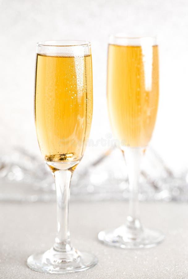 Verres de Champagne sur un contexte argenté de scintillement photo stock