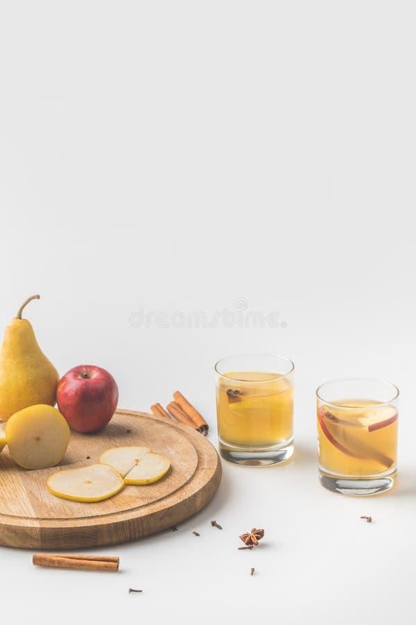 verres de cidre avec la pomme et la poire sur le conseil en bois images libres de droits