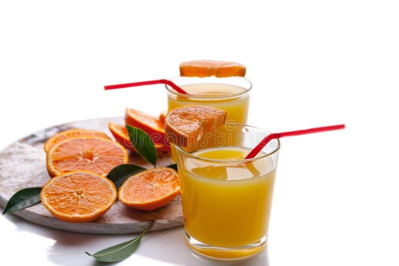 Verres de la vie avec le jus d'orange et tranches toujours oranges sur un fond blanc photo stock