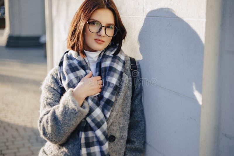 Verres de port attrayants de jeune fille dans un manteau marchant un jour ensoleill? images libres de droits