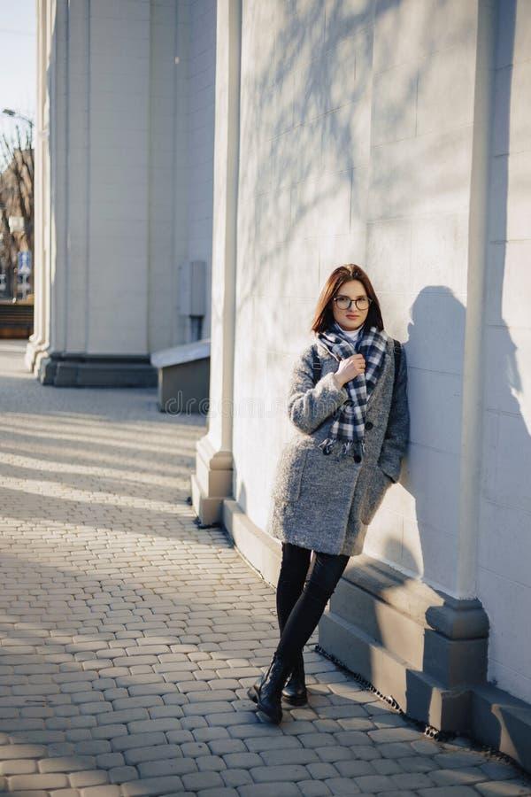 Verres de port attrayants de jeune fille dans un manteau marchant un jour ensoleill? photographie stock libre de droits