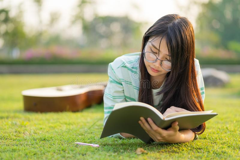Verres de port d'adolescente se couchant avec la guitare et les livres sur le champ au coucher du soleil image libre de droits