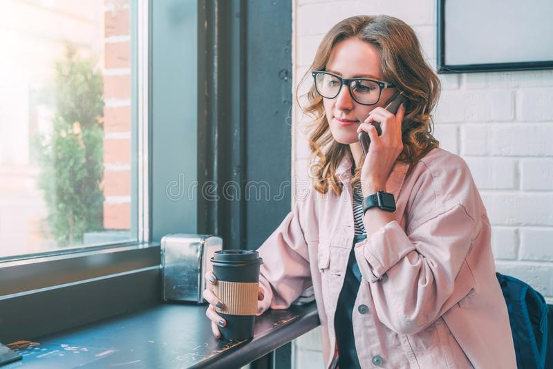 Verres de port de fille de hippie et veste rose de denim se reposant dans le café près de la fenêtre photos stock