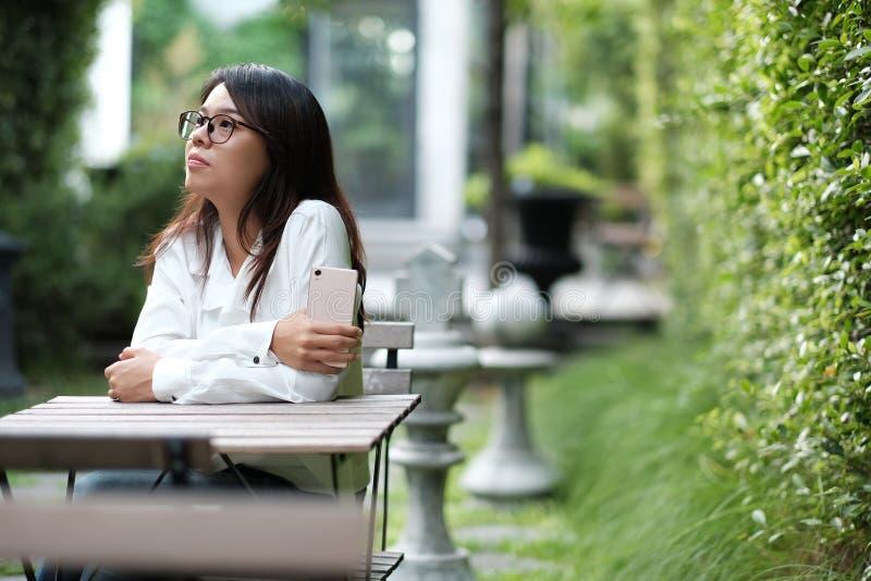 Verres de port de jeune femme se reposant au jardin public vert elle photo libre de droits
