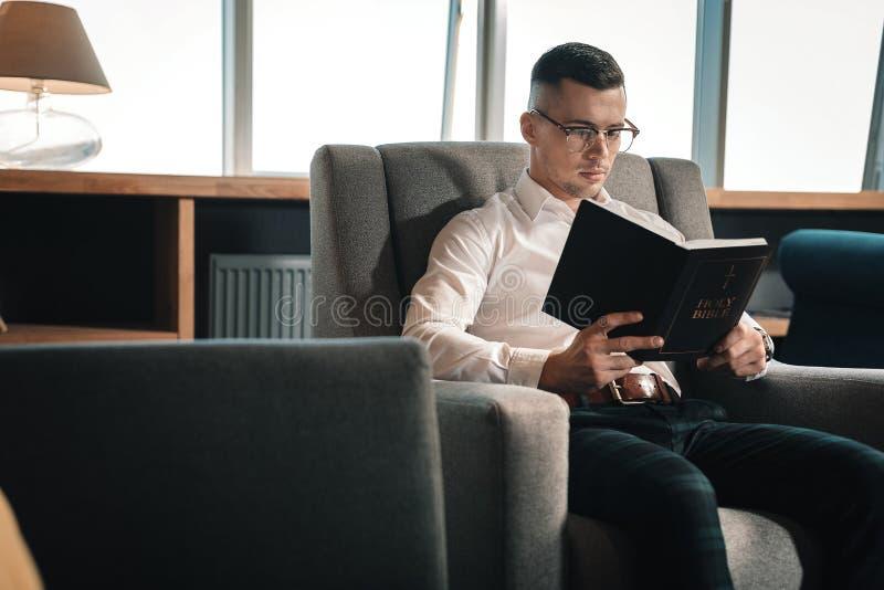 Verres de port de jeune homme futé lisant la Sainte Bible images libres de droits
