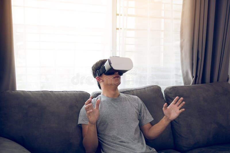 Verres de port de r?alit? virtuelle de jeune homme asiatique au salon pour admirer la r?alit? virtuelle photographie stock