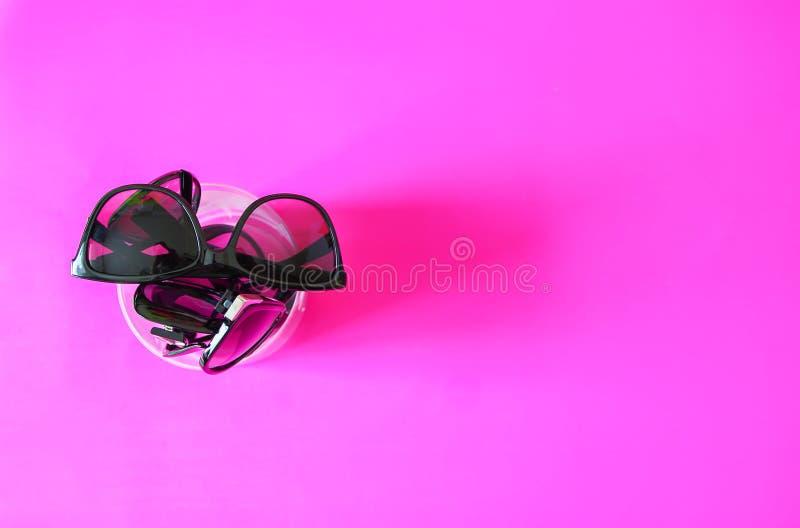 Verres de Sun sur le fond en pastel rose Verres avec les cadres noirs Accessoires de mode UV de protection d'oeil photographie stock