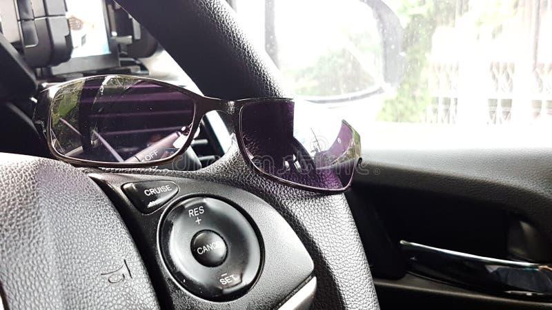 Verres de Sun sur le volant de la voiture moderne avec le fond d'éclat photo libre de droits