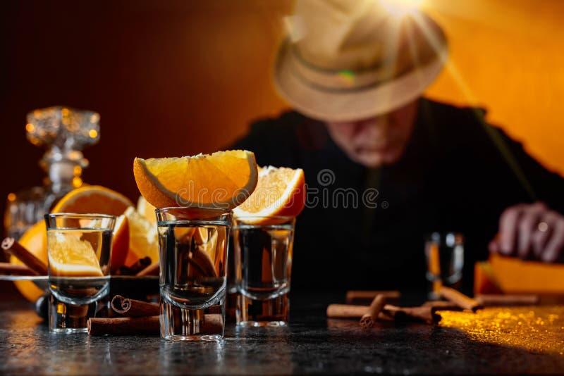 Verres de tequila avec des bâtons d'orange et de cannelle sur une table dans la barre photographie stock