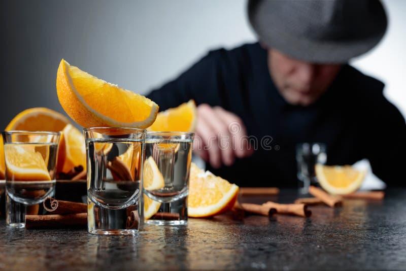 Verres de tequila avec des bâtons d'orange et de cannelle sur une table dans la barre images stock