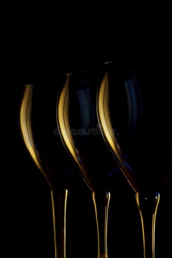 Verres de vin allumés par côté image stock