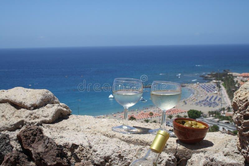 Verres de vin blanc avec le wiev de mer photographie stock libre de droits
