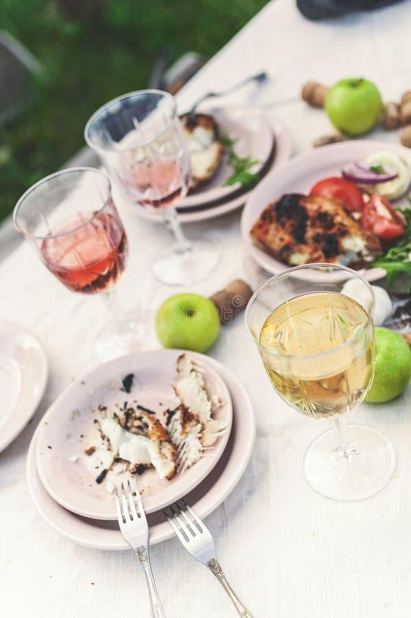 Verres de vin blanc et rosé, d'éclisses grillées, de légumes, de salade et de fruits sur la table Partie d'été dans l'arrière-cou images stock