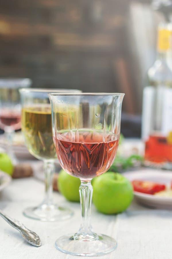 Verres de vin blanc et rosé, d'éclisses grillées, de légumes, de salade et de fruits sur la table Partie d'été dans l'arrière-cou images libres de droits