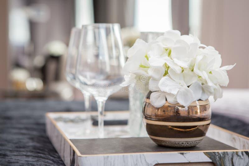 Verres de vin et vases à fleur vides dans un plateau sur le lit photos libres de droits
