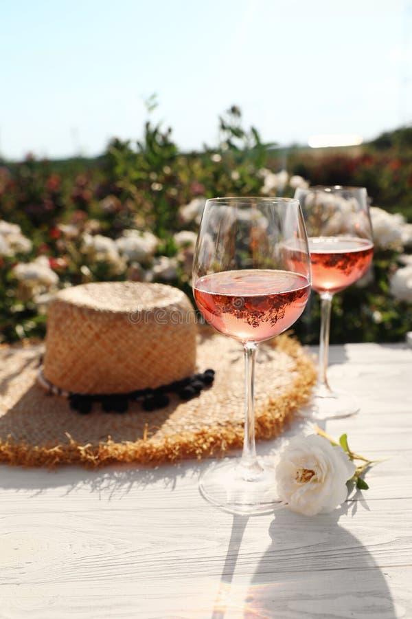 Verres de vin rosé, de chapeau de paille et de belle fleur sur la table en bois blanche photographie stock libre de droits