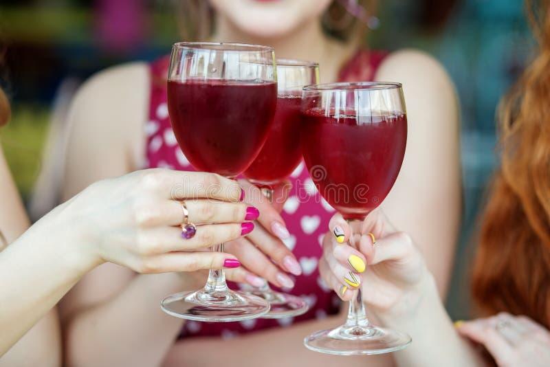 Verres de vin rouge dans des mains femelles Pain grillé à une partie Le concept de l'alcool, vacances photos stock